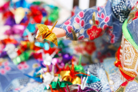 Miniature origami birds and a Japanese doll dressed in kimono. Shallow depth of field. Focus on the golden bird.