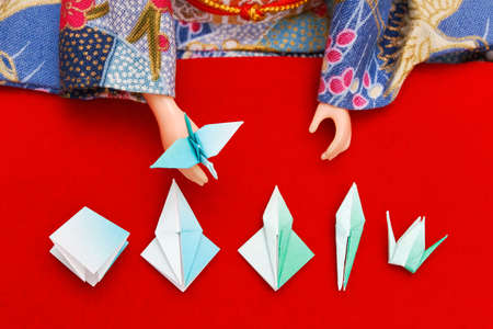 A Japanese doll dressed in kimono showing the steps to fold a paper bird
