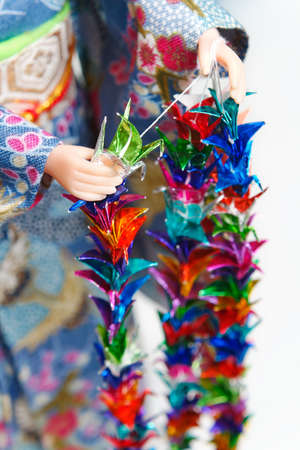 A Japanese doll in kimono arranging part of a Senbazuru. Shallow depth of field.