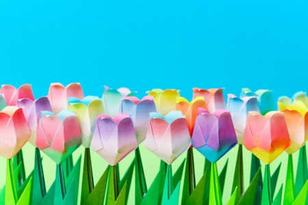 Paper tulips field with a blue background. Shallow depth of field. Focus on the front row. Stock Photo