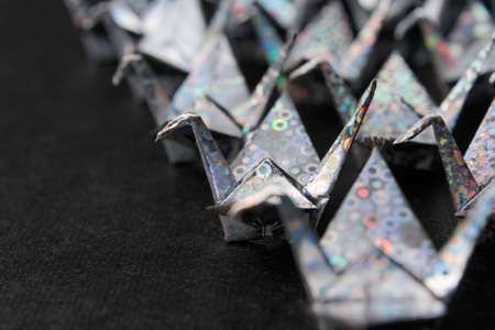 Rows of silver paper cranes facing the same direction. Shallow depth of field.  Stock Photo