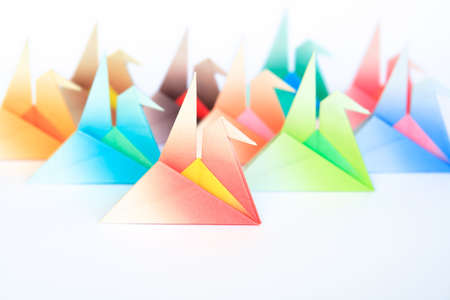 A group of colourful origami birds facing the same direction, on a white background. Shallow depth of field.