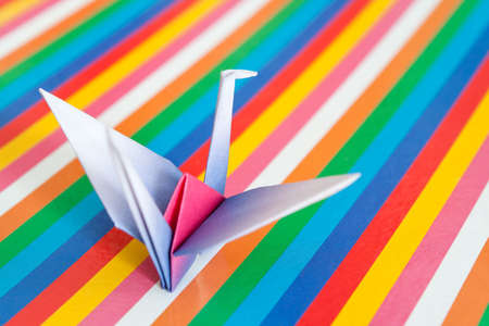 A single paper bird on a colorful stripes background. Shallow depth of field.  Stock Photo