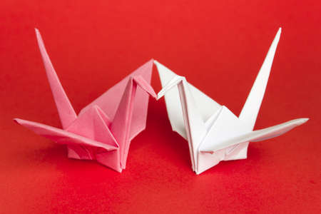 Two paper birds facing each other on a red background. Shallow depth of field. Stock Photo