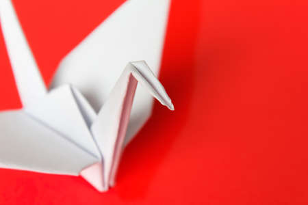 A white paper bird on a red background, shallow depth of field   Stock Photo