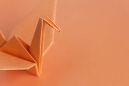 lonely bird: An orange paper bird on an orange background, shallow depth of field Stock Photo