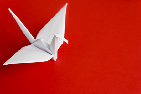 paper folding: A white paper bird on a red background Stock Photo