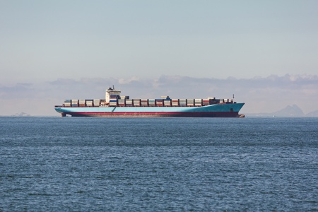 Cargo ship sailing in still water near Hong Kong
