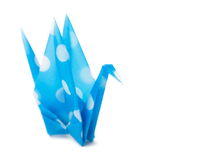 Semi-transparent cyan paper crane on white background. Very shallow depth of field. Stock Photo
