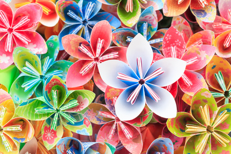 A pile of colourful Japanese Kusudama flower pieces. Shallow depth of field. Focus on the bluepink flower on top of the pile. Stock Photo