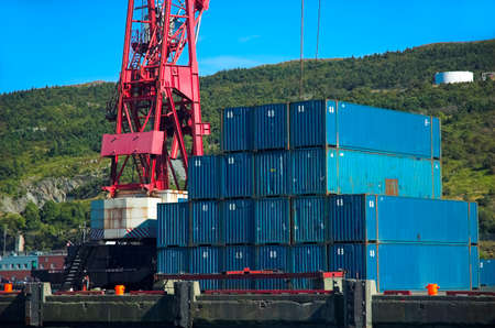 intermodal: Blue shipping containers beside red crane