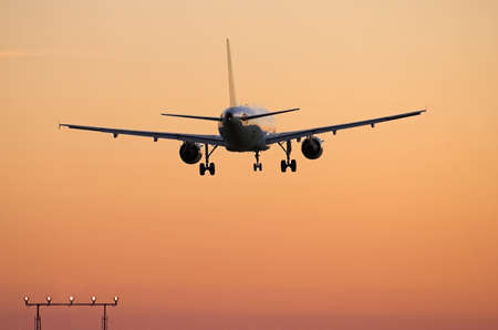 redeye: Rear view of airliner over the approach lights at major airport Stock Photo