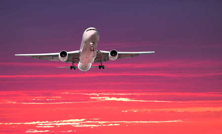 redeye: Widebody airliner on approach with colorful dramatic sky in the background Stock Photo
