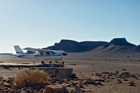 high desert: Small private airplane in desert. Shot in Namibia. Stock Photo
