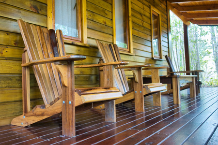 chalet: Row of wooden chairs on chalet terrace.
