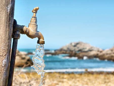 grifos: Agua corriente que fluye del grifo contra la playa rocosa. Filmada en Sudáfrica. Foto de archivo
