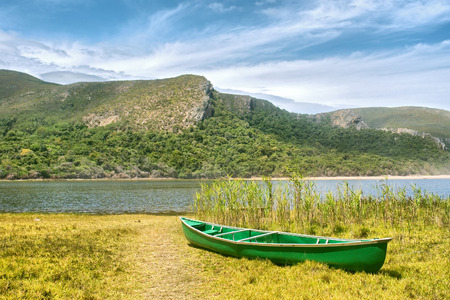 green boat: Green boat and lagoon. Shot in the Tsitsikamma National Park, Garden Route area, Western Cape, South Africa. Stock Photo