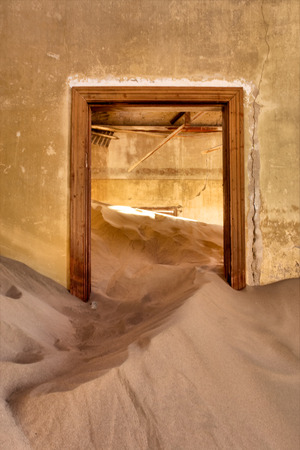 luderitz: Door of abandoned house in sand. Shot in Kolmanskop ghost town, Namibia. Stock Photo