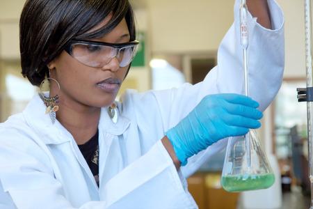 examenes de laboratorio: Enfocado investigador mujer africana trabaja con una copa en el laboratorio.