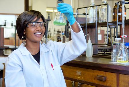 investigador cientifico: Investigador mujer africana feliz con el equipo de vidrio en el laboratorio