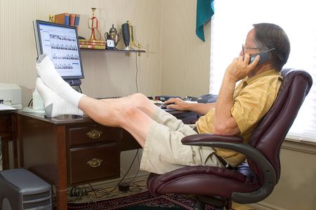 office desk: Man in his home office with feet on desk while talking on phone.