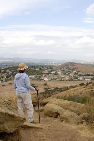 encroaching: A woman hiker viewing communities of families spreading into the foothills of the countryside.