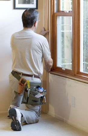 Homeowner installing molding around newly installed windows. Stock Photo - 629728