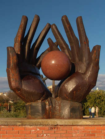 All of the world in the big hand! :-) Red marbe ball on the big matal hand