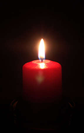 red candle light on black background in a glass holder Stock Photo