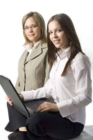 Two happy young manager ladies with notebook on white background