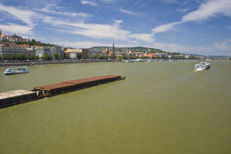 Budapest Danube with boats and barge under the blue sky