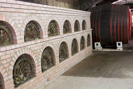 Antique wooden barrels in an old arched wine cellar.