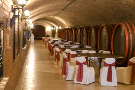 Antique wooden barrels in an old arched wine cellar in a catering event.