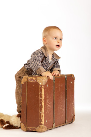Little boy with old brown suitcase goes into the world Stock Photo