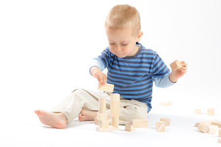 Little cute boy playing with wooden building blocks  Isolated on white  Stock Photo