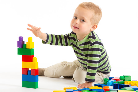 building blocks: Little cute boy playing with plastic building blocks. Isolated on white. Stock Photo