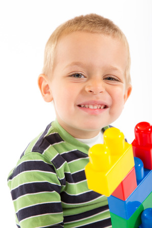 Little cute boy playing with plastic building blocks. Isolated on white. Stock Photo
