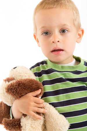 Little boy with his plush puppy.  Isolated on white. photo