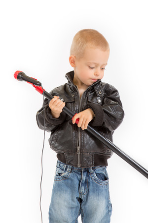 little rocker boy in leather jacket with a microphone stand