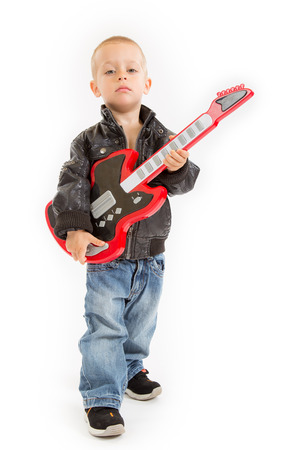 little rocker boy in leather jacket and blue jeans with his guitar Stock Photo