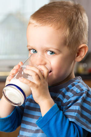 Young boy drinking milk out of glass in the kitchen Stock Photo