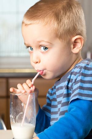 Cute little boy drinks milk using a drinking straw
