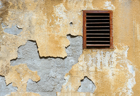 retro wall crumbling plaster coat and rusty ventilation grid Stock Photo