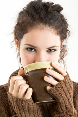 Brunette in knitted pullver drinking from a mug, with white background