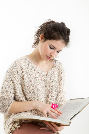 Brunette in knitted pullover sitting and reading a book, with white background