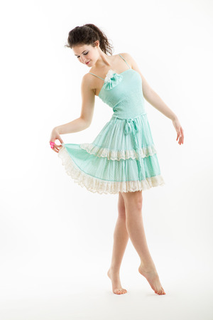 Young brunette in vintage style clothes is dancing, with white background Stock Photo