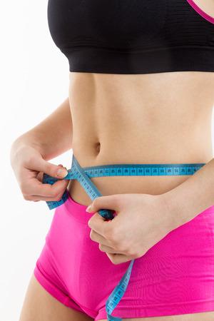 cintura perfecta: Muchacha de la aptitud que mide su shapeed perfecta de la cintura hermosa. Bajó de peso, con el fondo blanco