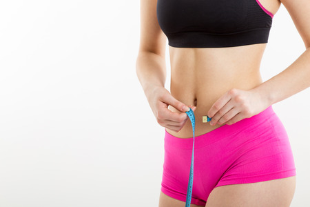 Fitness girl measuring her perfect shapeed beautiful waist. She lost weight, with white background