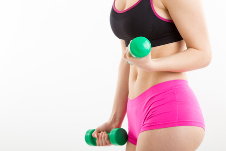Fitness girl in pink pants is coaching with green dumbbells, with white background Stock Photo