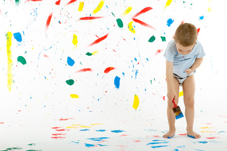 Adorable 3 year old boy child creatively stains on the wall, floor with colourful paint. Mess of paint on wall, floor and everywhere.